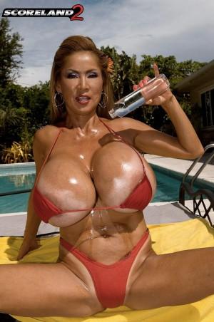 Chesty boob model Minka posing non nude outdoors in skimpy bikinis