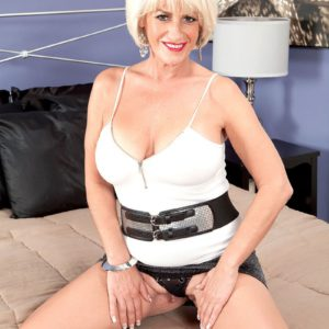 Mature lady Desire Collins flashes big tit while jerking cock