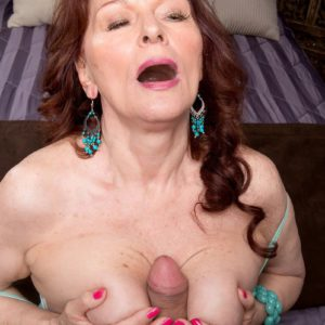 Redheaded granny Katherine Merlot gives a big cock titjob