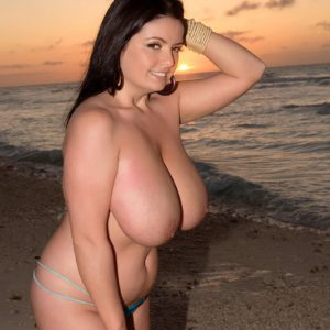Brunette babe Arianna Sinn exposing huge natural tits outdoors on beach