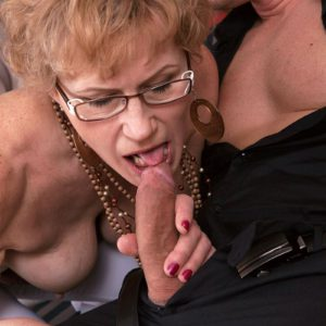 Glasses wearing mature woman exposes big boobs before giving a blowjob