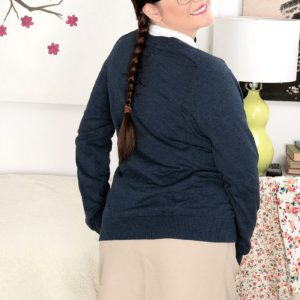 Pigtail and glasses attired solo girl Kate Marie unleashing large natural breasts