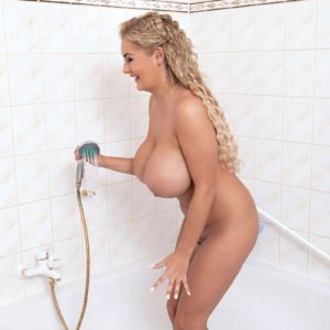Wet blonde babe Katie Thornton soaping up huge hooters in shower