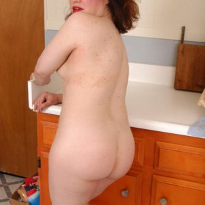 Mature redhead peels off translucent garb and lingerie to pose nude in kitchen