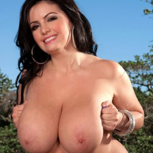 Plump brown-haired MILF Arianna Sinn displaying huge breasts and erect nips outdoors in high heels