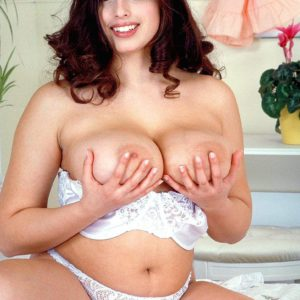 Round brunette adult movie star Kerry Marie uncovering enormous MILF tits from lingerie