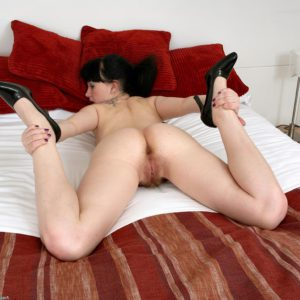 Spindly dark-haired solo girl pulling underwear down before opening up furry vag in high-heels
