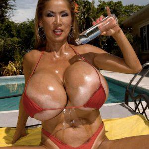 Top heavy Japanese stunner Minka oiling massive bikini garbed titties outdoors by pool