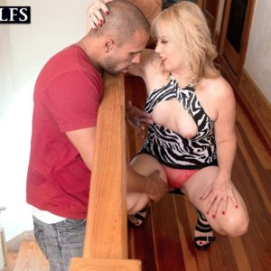 Aged blond cougar Rebecca Williams seducing junior boy for sex on bed