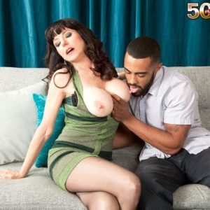 Black-haired MILF over 50 Karen Kougar seducing junior guy for sex on couch