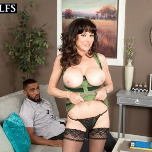 Black-haired MILF over 50 Karen Kougar seducing junior guy for sex on couch