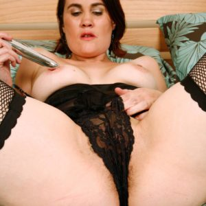 Elderly brunette doll in black pantyhose ramming sex toy into trimmed cunt in high heeled shoes