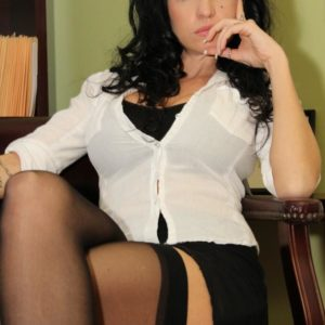 Glasses clad dark haired Emmanuelle London displaying bald upskirt honeypot in tights