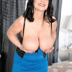 Senior brunette lady Elektra letting huge titties free from dress in high heeled shoes