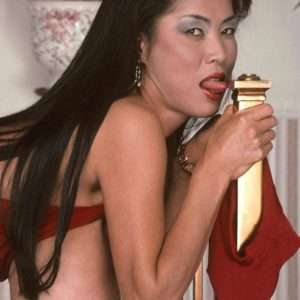 Asian MILF porno starlet Minka extracting humungous knockers from crimson dress in high heeled shoes
