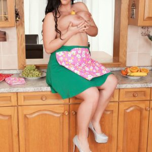 Black-haired stunner Juliana Simms letting large funbags loose from dress in kitchen