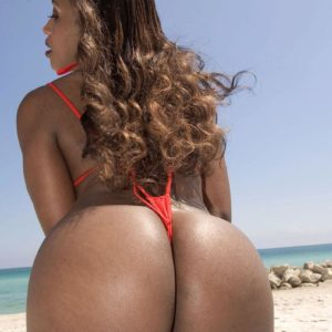 Black solo female Sapphira vaunting giant butt on beach clad crimson swimsuit