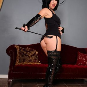 Brunette Dominatrix Belle Noir demonstrating ultra-cute and smooth-shaven fuckbox in ebony latex boots