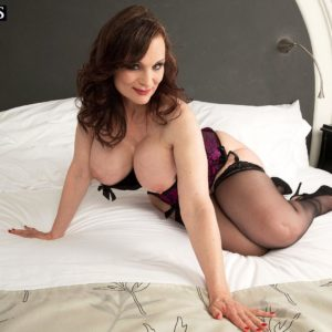 Dark-haired MILF over 50 Michaela O'Brilliant flashing huge knockers before delivering fellatio
