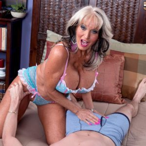 Hot over fifty MILF Sally D'Angelo displaying enormous juggs while seducing man for sex on bed