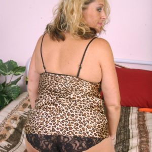 Chunky older golden-haired woman peeling off lingerie and panties before masturbating