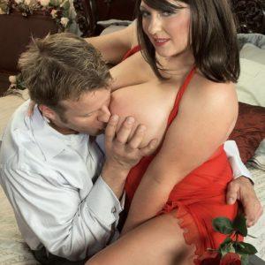 Dark haired MILF Angel Gee unsheathing large tits from see through dress for nip slurping