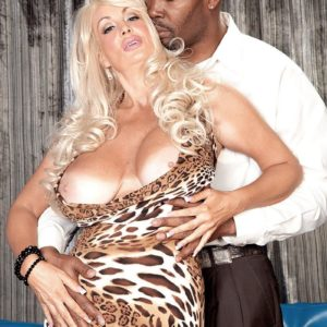 Lumbering blond MILF Brittany O'Neil revealing monster-sized knockers for ebony boy on leather chesterfield