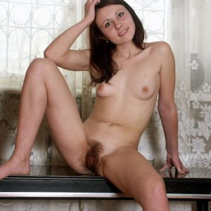Nude amateur dark haired solo female demonstrating fur covered cooter in bare feet on bench
