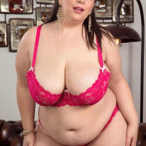 Plus-sized solo chick Mia Hotty disrobing down to pinkish brassiere and panty set on chesterfield