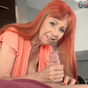 Redheaded grandma with great legs and large all-natural boobs delivering hand-job in kitchen