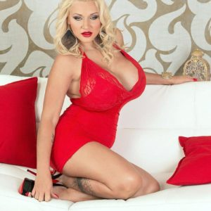 Sandy-haired MILF Dolly Fox letting large breasts loose from red sundress in heels