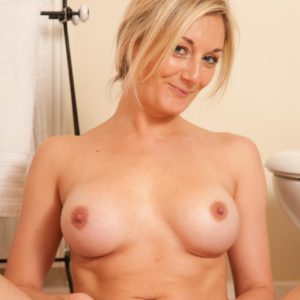 Senior ash-blonde solo model disrobing naked to pose nude in the wc
