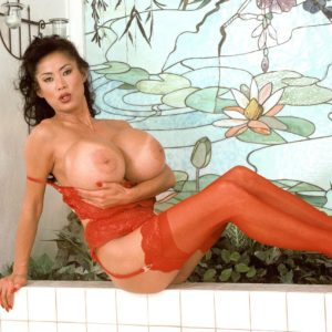 Top Asian adult video star Minka freeing her monster-sized tits from brassiere adorned red tights