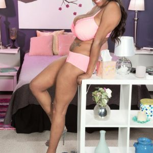 Black MILF Rachel Raxxx disrobing down to matching pink brassiere and panty set on bed
