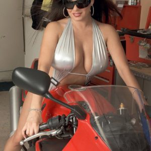 Brunette MILF Mia Starr uncovering enormous natural knockers on motorcycle in sunglasses