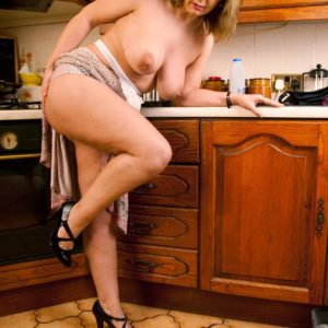 Mature platinum-blonde housewife lets her huge all natural boobies free in her kitchen
