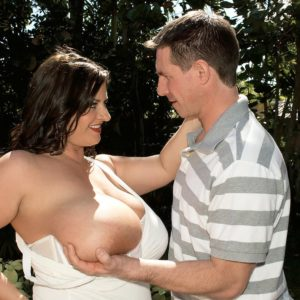 Thick brown-haired female Maria Moore having large juggs exposed outdoors