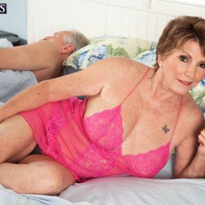 Big-titted red-haired grandma Bea Cummins jerking off massive boner while cuck spouse sleeps
