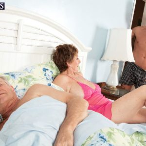 Big-titted red-haired grandma Bea Cummins jerking off massive boner while cuck spouse sleeps