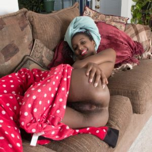 Ebony amateur with tiny floppy boobs uncovering fur covered ebony muff on sofa