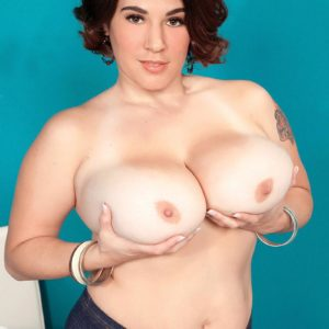 Thick brunette solo chick Elaina Gregory revealing funbags in jeans and pumps