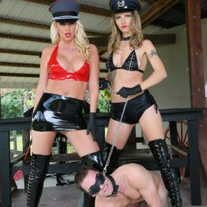 Two dominatrixes in hats and long boots lead masculine slave by a leash