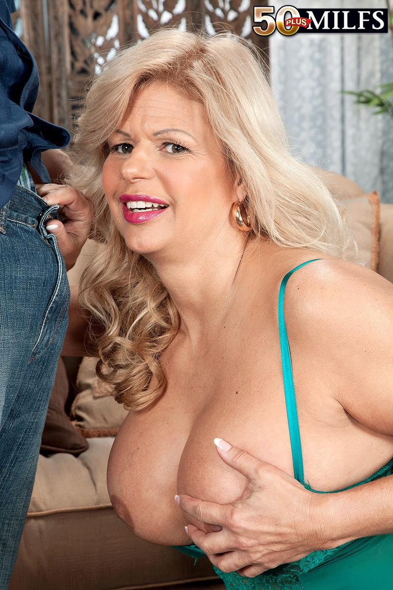 Aged platinum-blonde doll Miss Deb whips out her humungous juggs from her lingerie on a futon