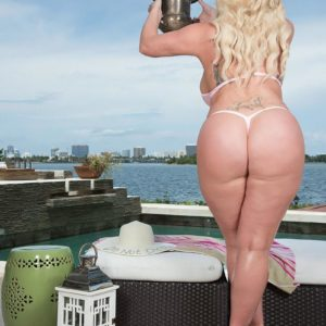 Ash-blonde BIG SEXY WOMAN Holly Wood struts about in a thong bathing suit next to the ocean