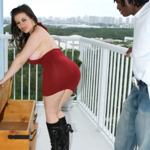 Chubby dark haired Daphne Rosen flashes off her massive ass in black boots on blacony