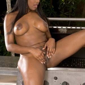 Enticing ebony MILF Barbie Banx unveils her giant juggs and giant arse on the patio