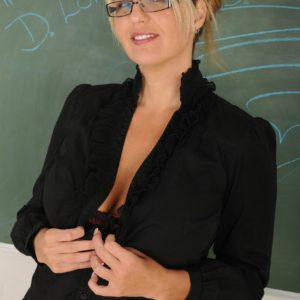 Older golden-haired dame outfitted glasses strips nude in front of chalkboard in classroom