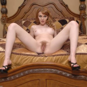 Redhead stunner with adorable tits parts the lips of her wooly beaver on her bed