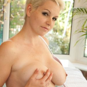 Senior platinum-blonde MILF with short hair uncovers her enormous all-natural tits after tennis