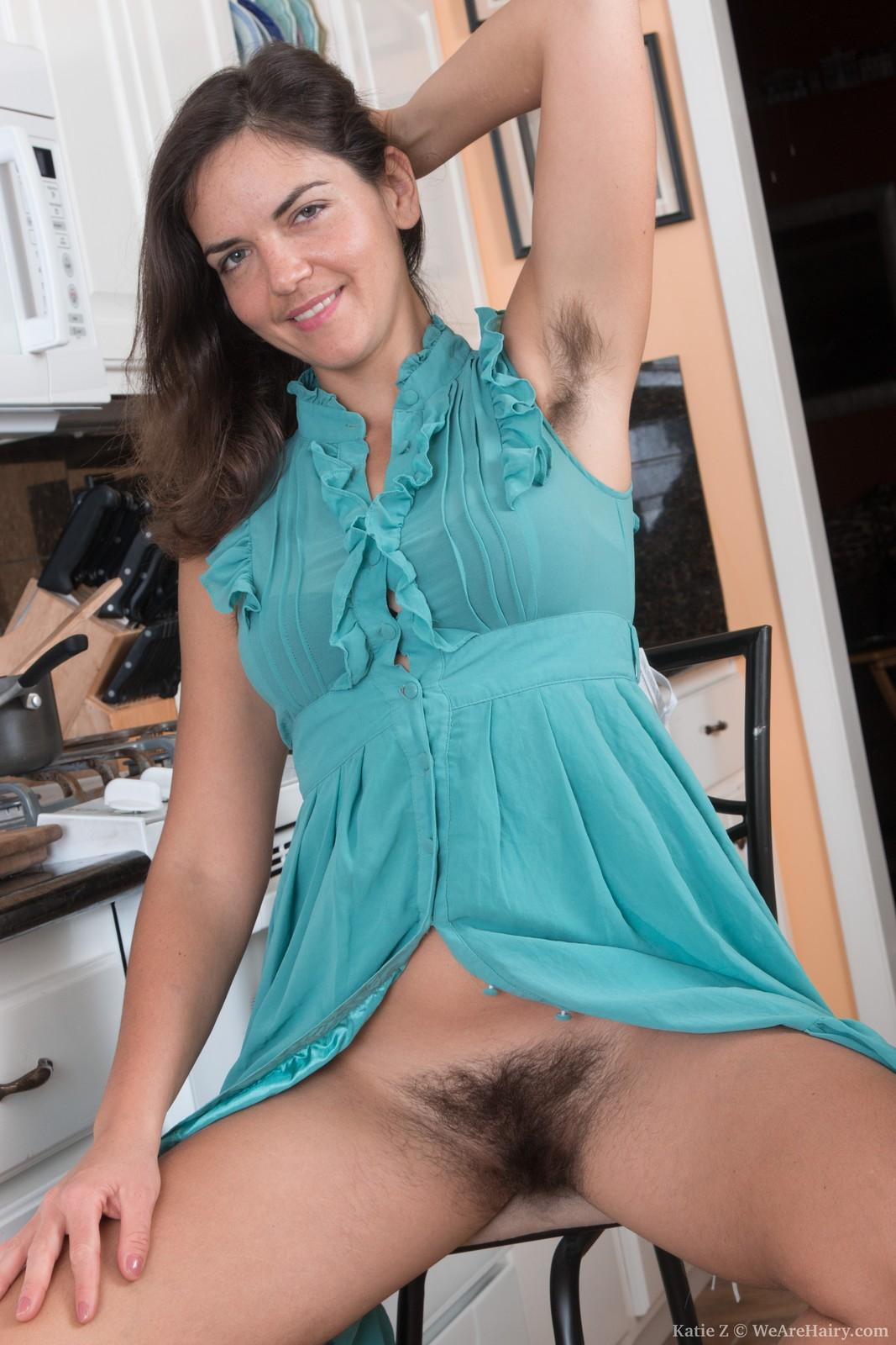 European first-timer Katie Z displaying hairy pits and all-natural pubic hair in kitchen
